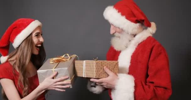 Mikulás és női segítő adnak ajándékokat