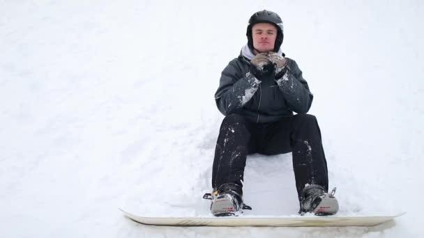 Snowboarder trägt Helm zur Sicherheit, sitzt auf Schnee