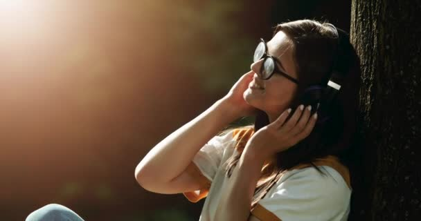 Woman in Headphones Listening to Music in Park