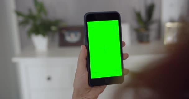 Žena držící na zelené obrazovce telefon