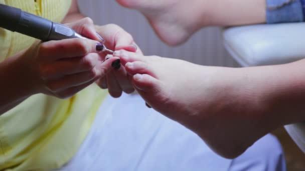 Meister Fußpflegerin macht Pediküre Gerät für Kunden im Beauty-salon