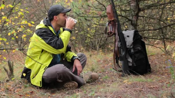 kaukázusi Férfi vadász erdei pihenés. tea ivás. vadászpuska, lőszer, hátizsák, a háttérben