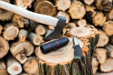 axe, monocle and tourist knife case on the stump, firewoods on the background