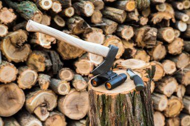 axe, binoculars and tourist knife case on the stump, firewoods on the background