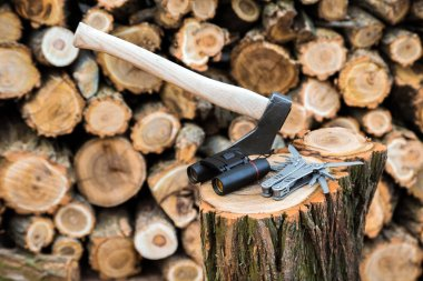 axe, binoculars and multitool knife case on the stump, firewoods on the background