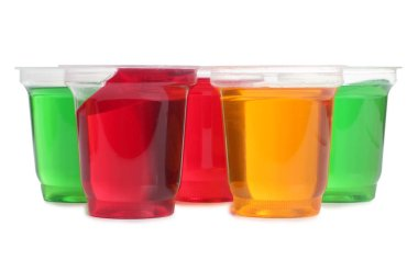 Jam in plastic cups with raw fruit on white background