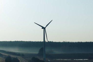 Silhouette of wind generator near empty road at sunrise