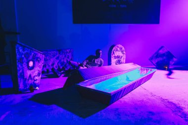 October, 28-29, 2017 - Minsk, Belarus: Art space, Party dedicated to HALLOWEEN, young man sitting behind coffin in club