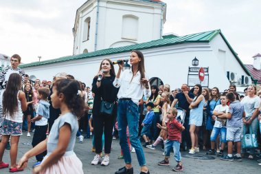 September 1, 2018 - Minsk, Belarus: Street festivities in evening city, Two girls with microphones singing on street in front of group of people