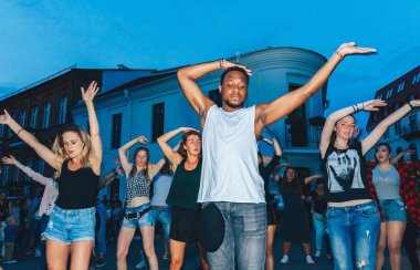 July 21, 2018 - Minsk, Belarus: group of happy young people dancing on square in evening
