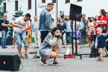 July 21, 2018 - Minsk,Belarus: Street walks. Girl with camera takes pictures on street in front of group of people