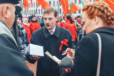 November 7, 2018 - Minsk, Belarus: Anniversary of Great October Socialist Revolution, group of people standing on square with flags and chatting