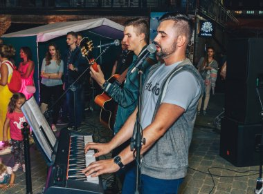 September 1, 2018 - Minsk, Belarus: Two men with an electronic piano and guitar performing concert in front of many people on street