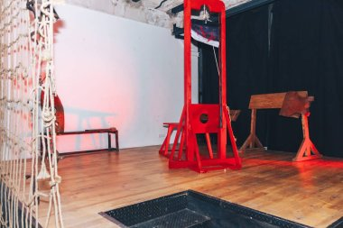 red wooden guillotine for execution of people standing on stage