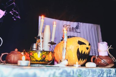 Candles and pumpkin with devices for tea drinking on table during halloween party