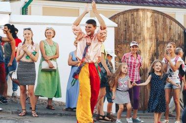 August 4, 2018 - Minsk, Belarus: Street festivities in evening city. man in clown costume dancing in front of people on street
