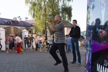 August 4, 2018 - Minsk, Belarus: Street festivities in evening city. man with balls doing performance in front of group of people on street