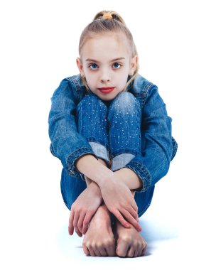 Young beautiful girl in denim suit sitting barefoot on white surface