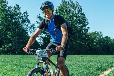 May 26-27, 2018 - Naliboki, Belarus: All-Belarusian amateur marathon Naliboki, man on bike riding along path to field