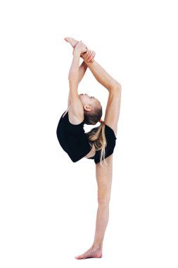 A little girl in a gymnastic costume raises her leg