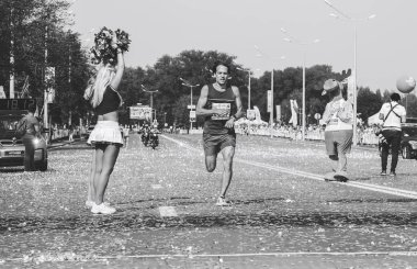 September 9, 2018 Minsk Belarus Half Marathon Minsk 2018 A man runs along the road . Confetti flies in the air. Festive mood.