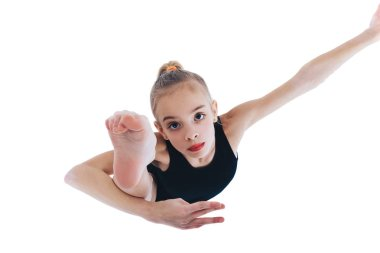 A little girl in a gymnastic costume raises her leg n Top view