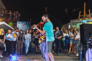 September 1, 2018 Minsk Belarus Street festivities in the evening city A man with a violin plays in front of people on the street