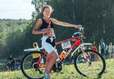 May 26-27, 2018 Naliboki,Belarus All-Belarusian amateur marathon Naliboki Girl with a medal standing next to a bike in the park