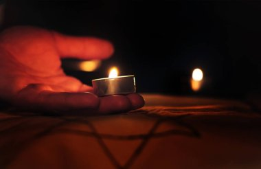 Burning candles over the Star of David on a black background in memory of the dead. A symbol of remembrance of the victims of the genocide of the Jew
