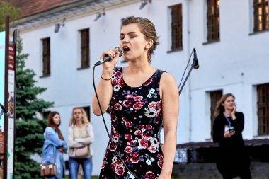 May 25, 2019 Minsk Belarus A street concert in which a close-up of a beautiful woman with a microphone sings on the street
