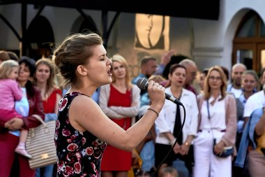 May 25, 2019 Minsk Belarus A theatrical performance in which a close-up of a beautiful woman with a microphone sings on the street