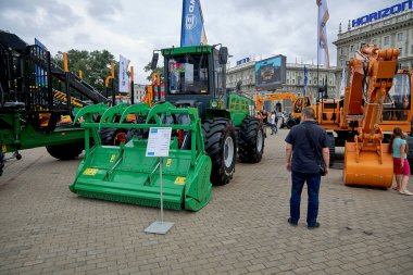 July 3 2020 Minsk Belarus People walk among the exhibition of construction and agricultural machinery arranged on the square stock vector