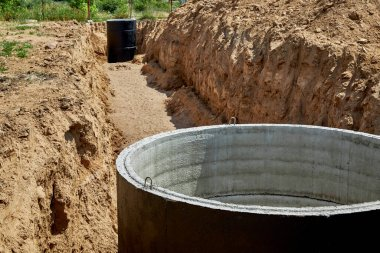 Concrete wells covered with waterproof mastic in a pipe-laying trench