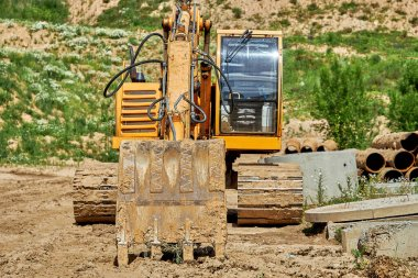 A large excavator stands next to concrete products at the construction site for the reconstruction of the old water supply network