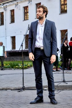 May 25, 2019 Minsk Belarus A handsome actor in a black suit with a beard stands at a street concert