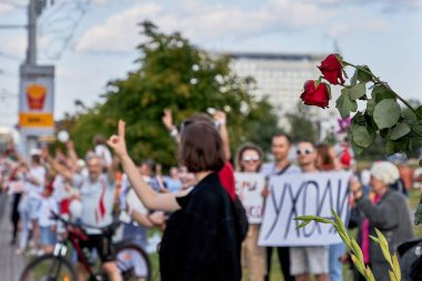 Red roses against the background of protesting people