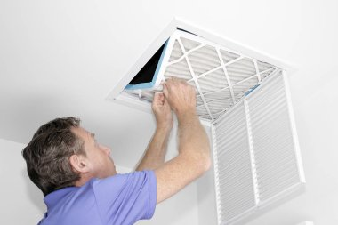 Man Removing Dirty Air Filter, Mature man taking out a dirty air filter from a home ceiling air return vent. Male removing a dirty air filter with both hands in a house from a HVAC ceiling air vent.