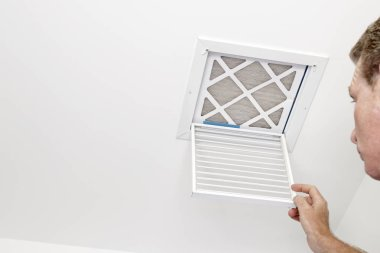 Man Opened a Vent to a Dirty Filter. Mature adult opening a small square HVAC air intake vent revealing a dirty air filter in the ceiling. Man opened a a vent grill cover to a dirty ceiling air filter