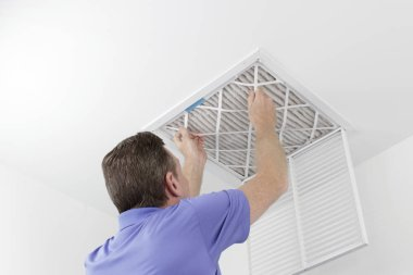 Person Removing Ceiling Air Filter. Caucasian male removing a square pleated dirty air filter with both hands from a ceiling air duct. Guy taking out an unclean air filter from a home ceiling air vent.