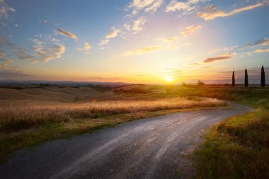beautiful winding country road leading through rural countryside in the Italy Tuscany District with evening sunlight.