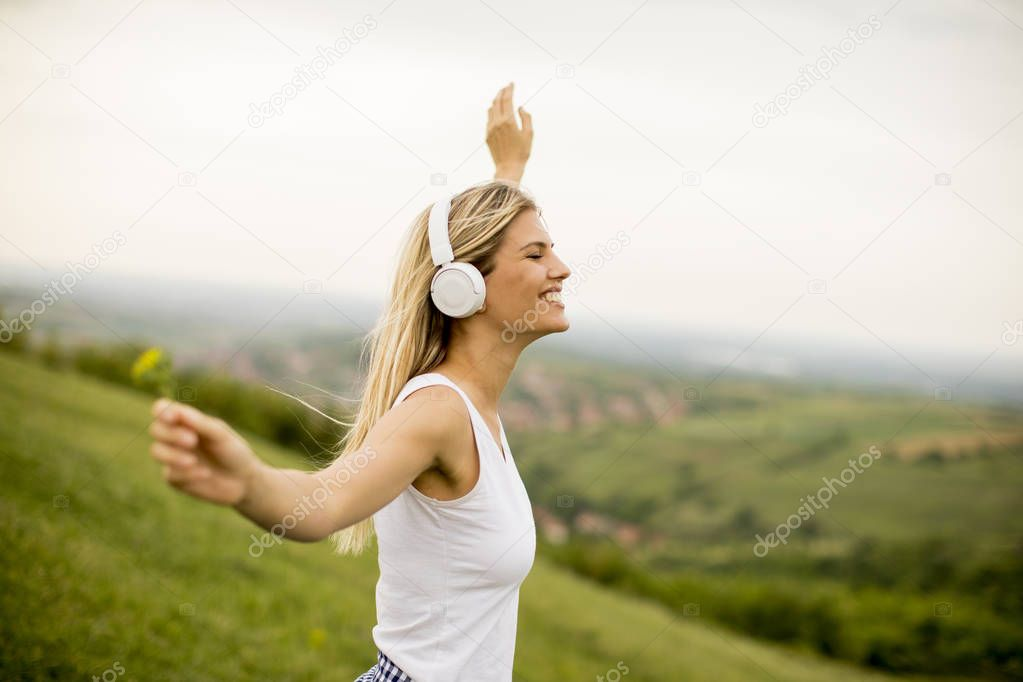 Happy young woman in nature listening to music on headphones