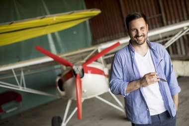 Handsome young man in the airplane hangar