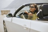 Fotografie Young woman with sunglasses driving her convertible top automobile on bright sunny day near sea