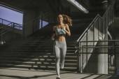 Hezká mladá žena běží v městském prostředí