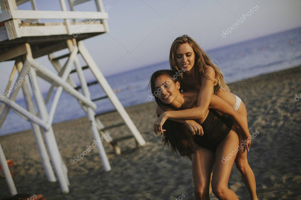 Two pretty young women having fun on the beach at summer