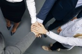 Fotografie Closeup of young coworkers putting hands together as symbol of unity in the office
