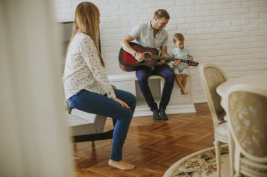 Happy family with guitar at home