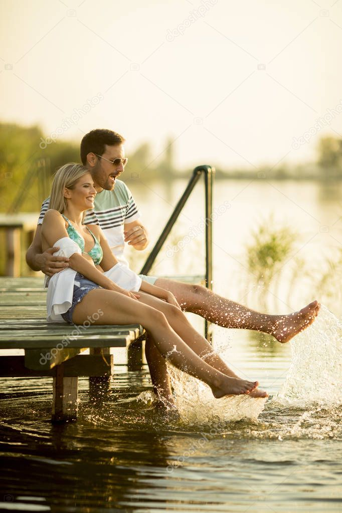 Romantic couple sitting on the wooden pier on the lake at sunny day