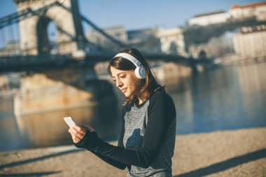 Young athlete woman with mobile phone on the bridhe in Budapest, Hungary