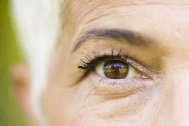 Close up view at wrinkled eye of beautiful lady stock vector